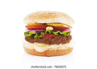 Big hamburger with fresh vegetables isolated on white.