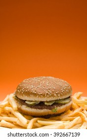 Big hamburger surrounded by french fries on orange background with copy space