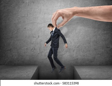 Big hand is bringing a businessman over a gap in the floor on gray background. Succes concept. Business idea. Progress and solution