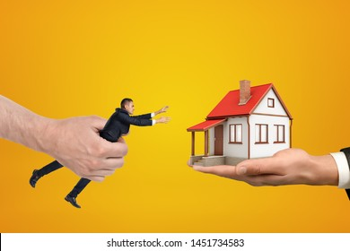 Big hand on the left holding small businessman reaching out with his both hands for small house standing on palm of the other hand on the right. Real estate. Mortgage problems. Building permit.