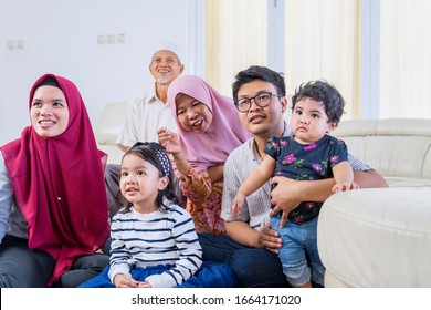 Big happy Asian muslim family watching television happily, while relaxing in the living room