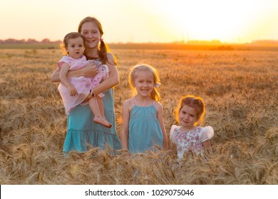 big happy family. four girls of different ages at the wheat field