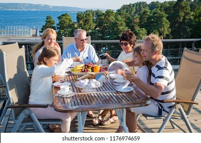 Big happy family having breakfast outdoors on terrace together, sitting around table, drinking coffee. Beautiful sea view, warm summer morning. Family bonds concept