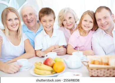 Big happy family looking at camera by dinner table