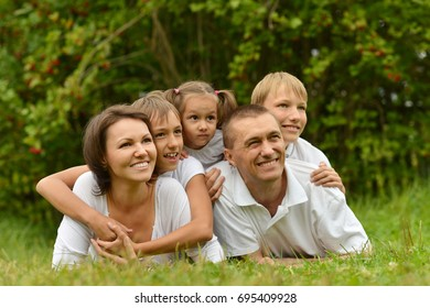 Big happy family lying on green grass and looking at camera