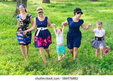 Big happy family on a walk in the park. Grandmother, daughter and granddaughter walk in the spring. Women of all ages have fun together