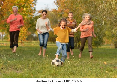 Big happy family playing football in autumn park