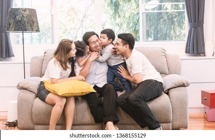 Big happy family sitting on sofa and childen kissing and smiling uncle in living room. Love family concept.