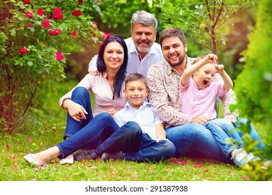 big happy family together in summer garden