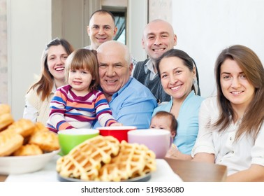 Big happy three generations family drinks tea with baked