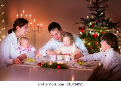 Big happy young family with three children enjoying Christmas dinner celebration, parents and kids - teen age boy, little toddler girl and baby in a dark dining room with candles and Xmas tree