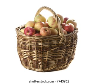 big harvest of apples in woven basket isolated on white background