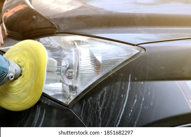 Big headlight cleaning on the car with power buffer machine at service station,Before and after cleaning car concept with a mechanic cleaning the headlights of a car using a power buffer machine