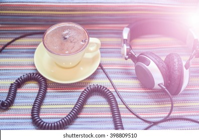 big headphones and cup with coffee on the colorful tablecloth