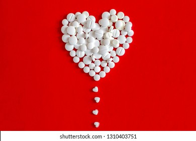 Big heart made from pills droping hearts shaped small pills one by one. Take care of your heart's health.
