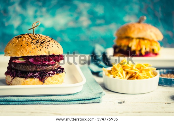Big homemade Burger with meat, fermented red cabbage, beet dip and potato wedges on a white ceramic plate. Rustic pastel style. Toned image.