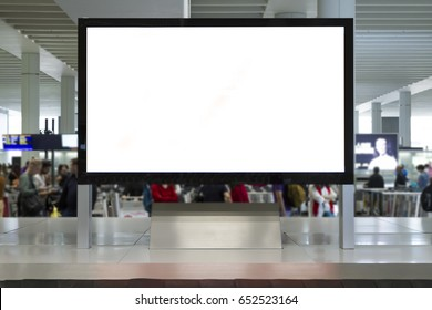 Big Horizontal Blank White Billboard Screen in airport. People are waiting luggage and talking at background. Selective Focus.