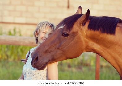 Big Horses head on womans shoulder. woman embrace brown horse