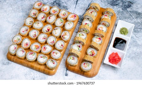 Big hot sushi set. 50 pieces. Hot sushi rolls on wooden tray isolated on marble. Wasabi, soy sauce and gari in plate isolated on marble.