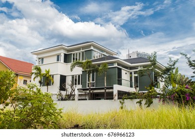 big house with garden and blue summer sky