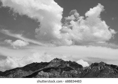 Big huge massive puffy white clouds floating over the black back lit Catalina mountains on a sunny day in Tucson Arizona black and white