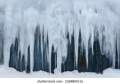 Big icicles on the glass. Frozen window. Winter frost in the extreme North. Cold weather. Fabulous Christmas and new year mood, as if in an ice world. Magadan, Russia. Texture perfect for background.