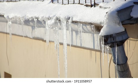 Big icicles on snow covered old roof edge wiyh downpipe intake on residential stone house at Sunny winter day