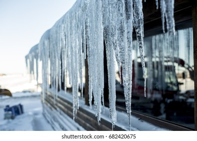 Big icicles stretching from a roof of a house  on a freezing cold winter day