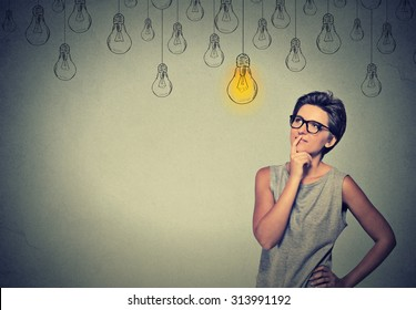 Big idea. Happy smart girl with glasses and solution lightbulb above head. Solving a problem creative idea concept
