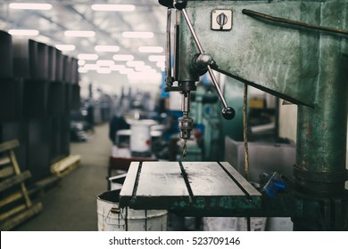 Big industrial driller machine. Metallurgy industry. Interior details from factory for production of heavy pellet stoves and boilers. Extremely dark conditions and visible noise. Focus on foreground.
