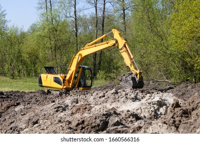 Big industrial excavator working on swamp at sunny day