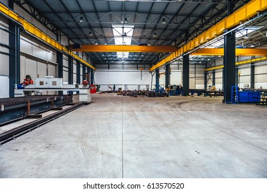 Big industrial hall with CNC Plasma laser cutter machine and metal profiles