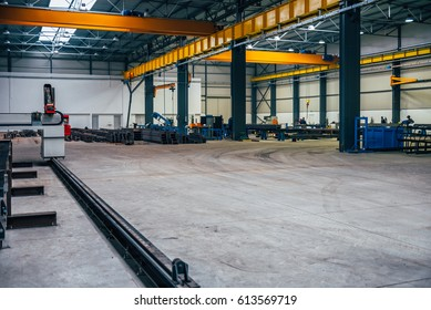 Big industrial hall with various machines and metal profiles