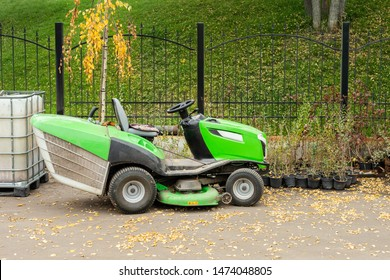 Big industrial lawnmower machine standing at parking in city park. Green lawn grass mower tractor at municipal street service area