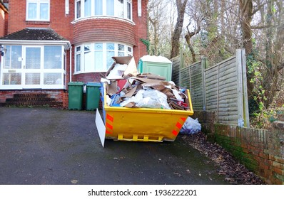 Big industrial rubbish bin in front of brick house with space to add text for background use, on side of heavy skip, driveway floor. Renovate, removal, recycle and home clearance concept.