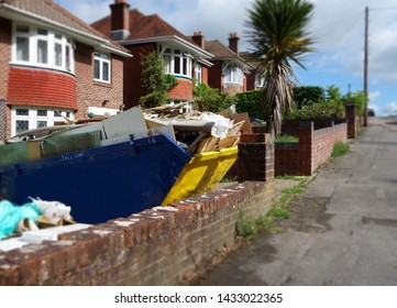 Big industrial skip on driveway. Selective focus on the metal bin full of building material with space to add text in front of skip, on blurry background of brick wall & footpath. Renovation concept.