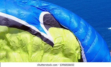 big inflated sail of a paraglider just before departure in the colors yellow and blue