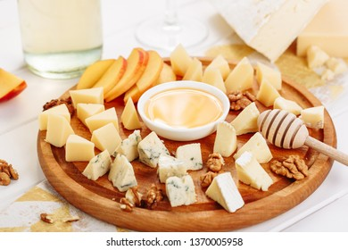 Big Italian Cheese Board Gourmet Food with Honey Side View. French Cheeseboard with Brie, Parmesan and Mozzarella Assorted. Blue Cheddar, Gouda and Walnut Appetizer Dessert Platter