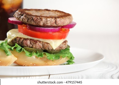 Big juicy traditional American burger with grilled meat and slices fresh vegetables closeup on a white plate on a wooden table. Food and beverages. Selective focus with shallow depth of field