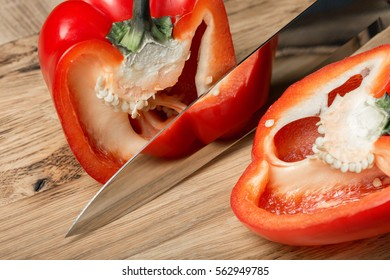 Big kitchen knife cut a bell pepper on two parts close up