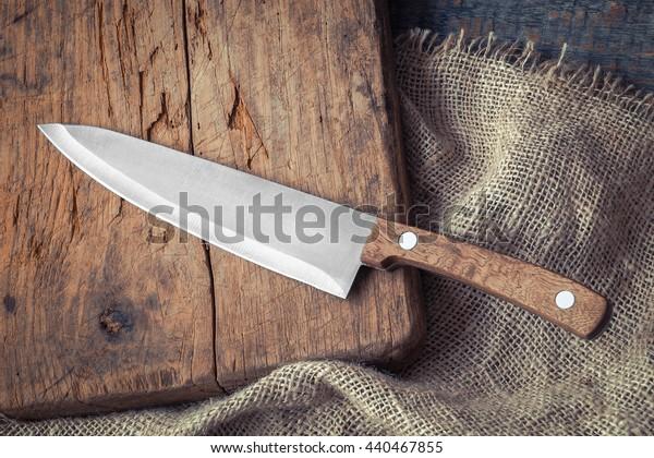 Big kitchen knife lying on an old cutting board