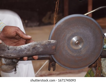 A big knife like object sharpened by an Indian man in his bicycle  powered stone wheel.