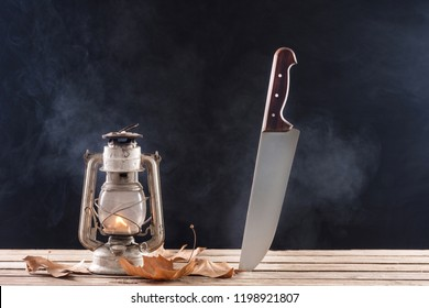Big knife stabbed in wooden desk and old gas lamp burning and fall dry autumn leaf on table. Black and dark smoky and foggy background. Horror and Halloween concept
