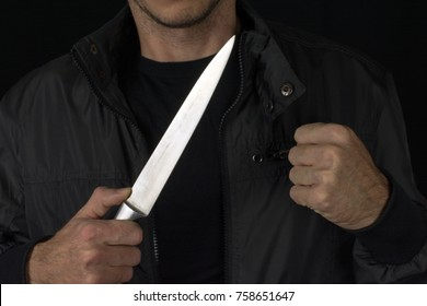 big knife in young man hand of a  black jacket clenched fist. Defend Against a Knife Attack concept close up, selective focus , blurred dark background