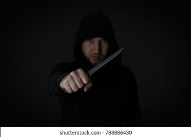 big knife in young man hand of a black jacket clenched fist. Defend Against a Knife Attack concept close up, selective focus , blurred dark background.