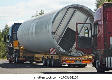 Big large pipe on a low-frame trawl semi truck, oversized cargo transportation logistics on lowbed long vehicle