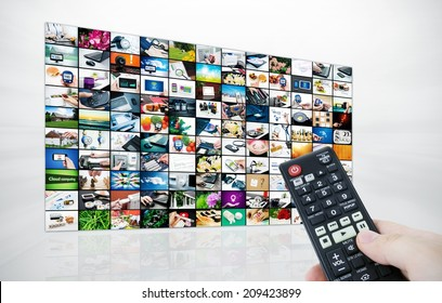 Big LCD panel with television stream images and remote control in hand