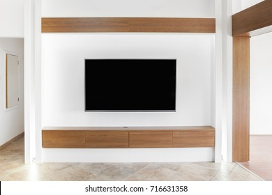 big led TV on white wall with wooden shelf
