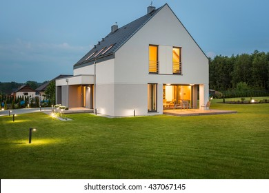 Big light house in new design with wide lawn and outdoor lighting, night view