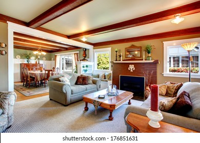 Big living room with grey carpet floor, ceiling beams, stoned background fireplace. Room furnished with sofa, rustic coffee table and open to big dining room.